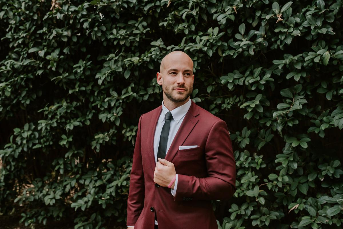 Julian dressed in a burgundy suit with a black tie