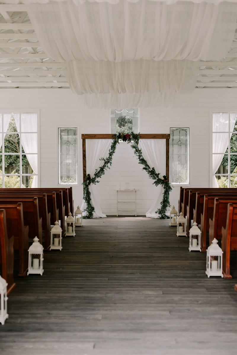 Wooden ceremony arch with white draping and greenery garlands