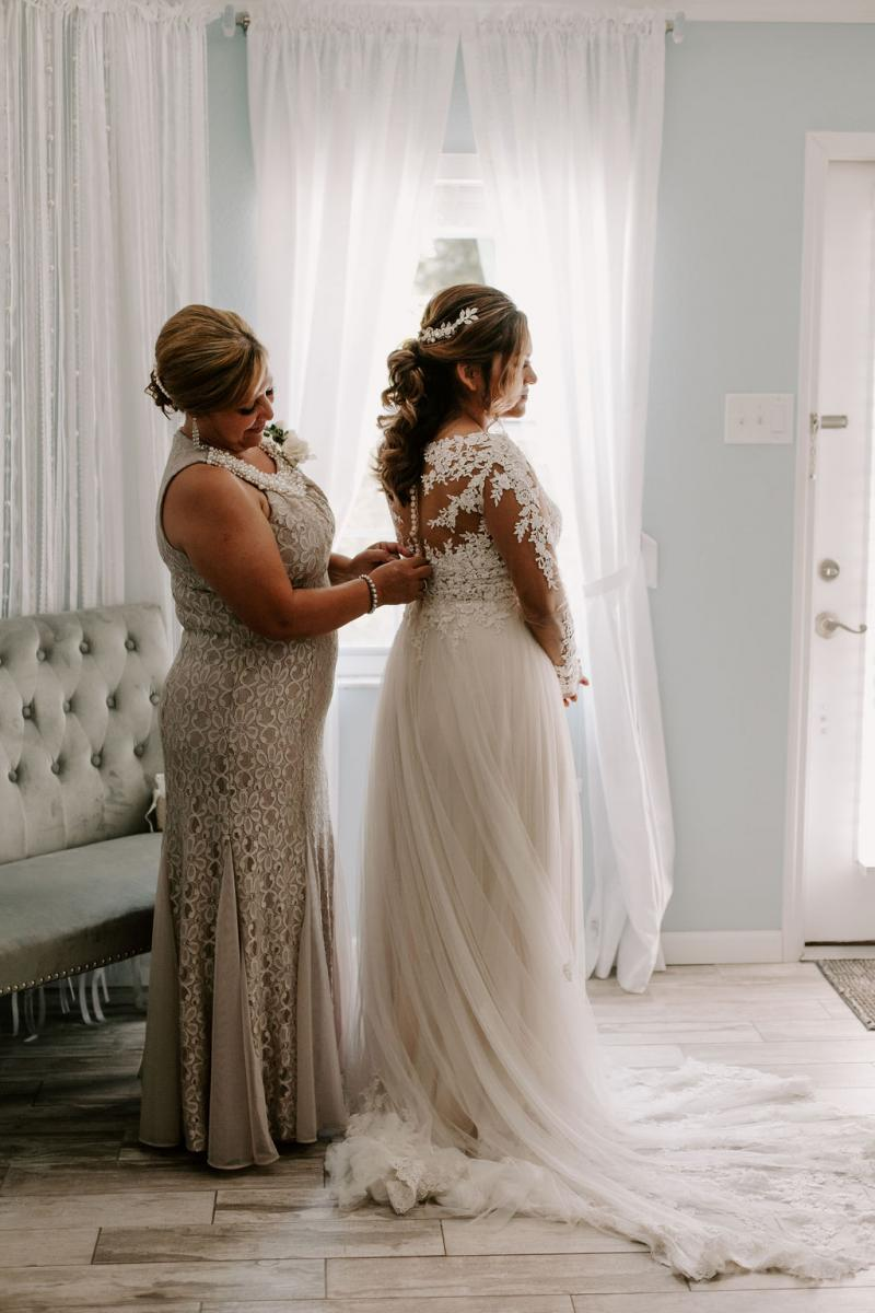 Bella's mom helping her get her dress on