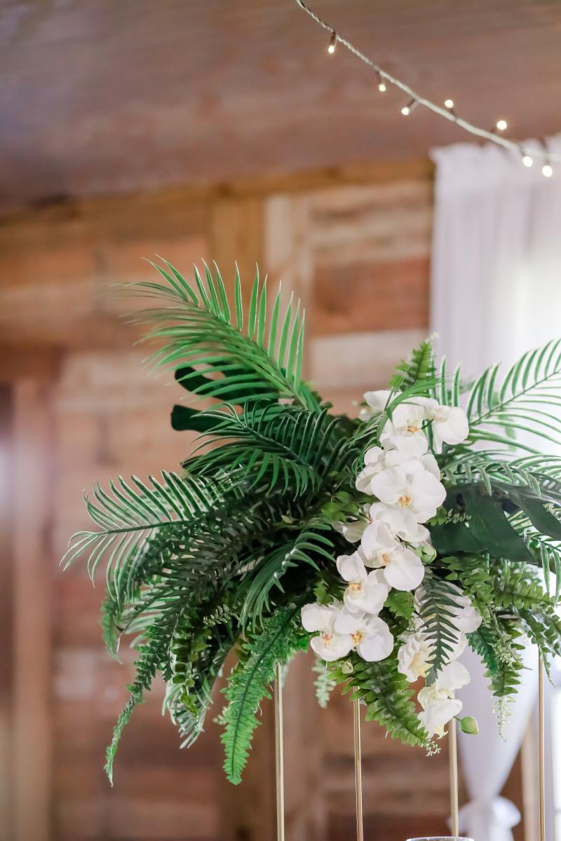 Up close photo of the large arrangements with palm leaves and white orchids