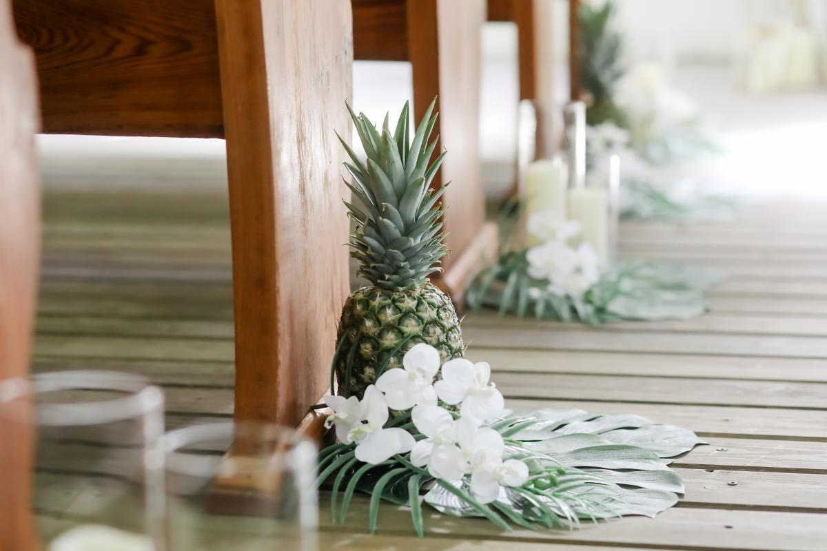 Fresh pinapples, white orchids and palm leaves line the ceremony aisle