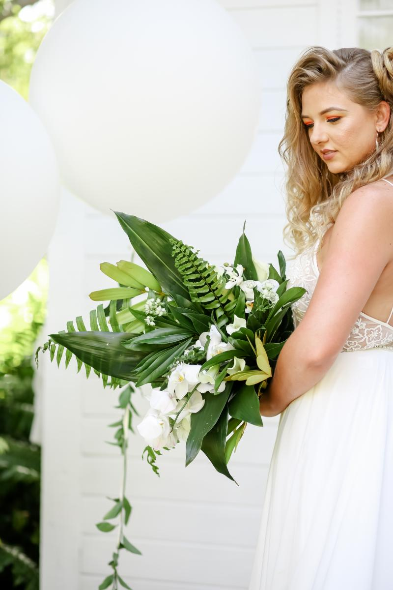 Fresh tropical bouquet with palm leaves and white orchids