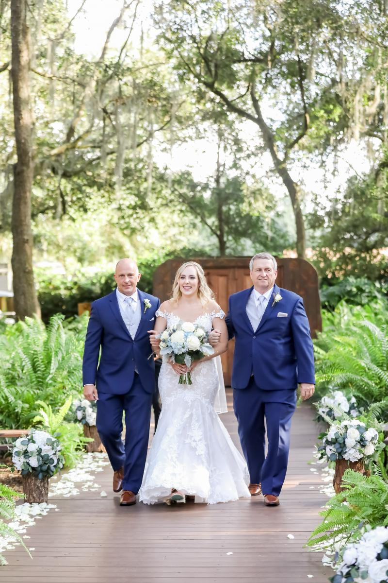 Ellie walking down the aisle with both of her fathers