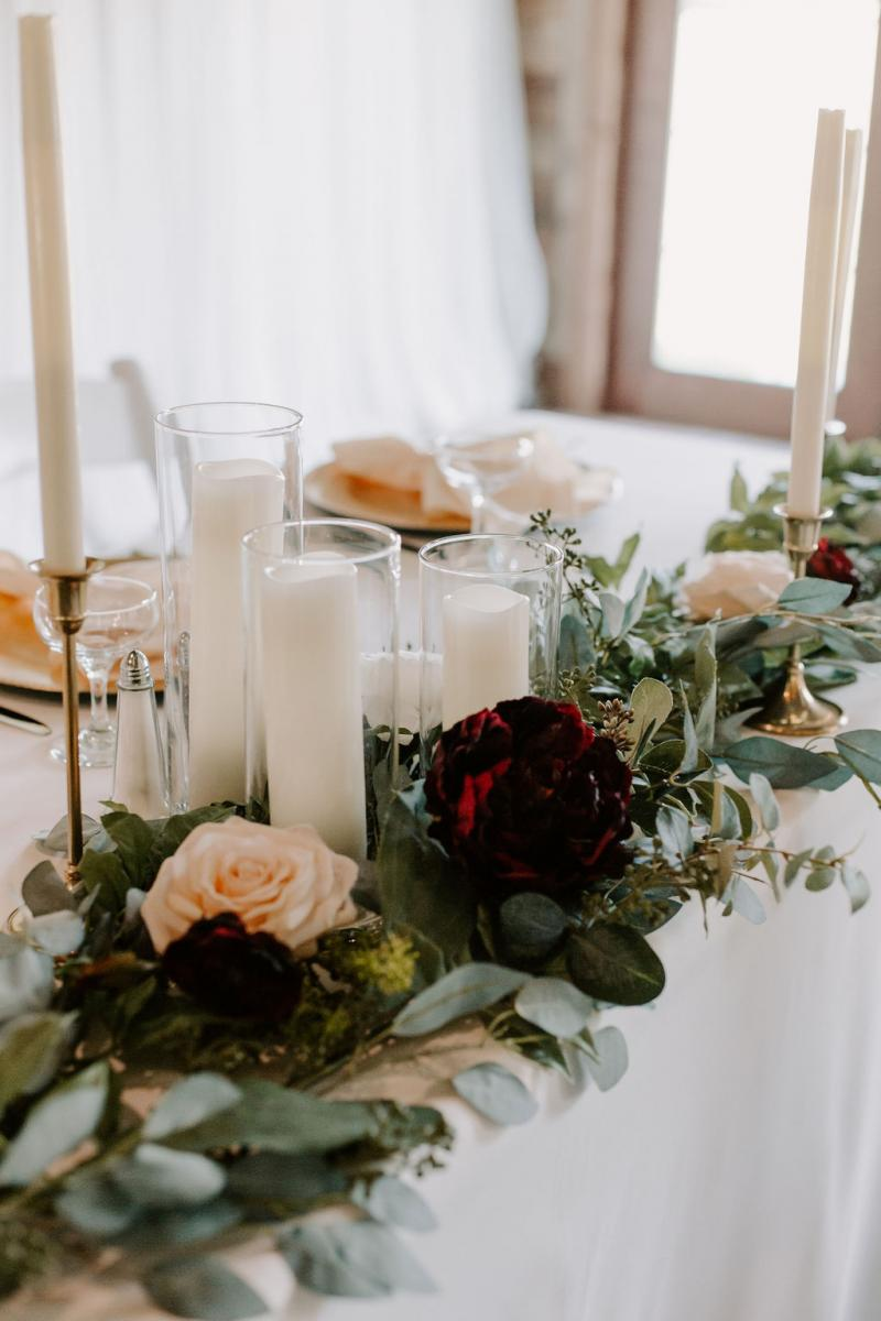 Garlands of greenery and burgundy and blush flowers